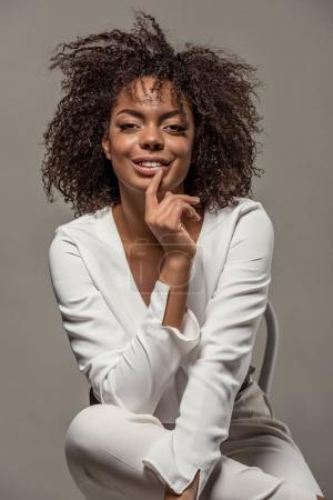 Young sensual african american woman in white shirt with finger on lips sitting on chair isolated on grey background