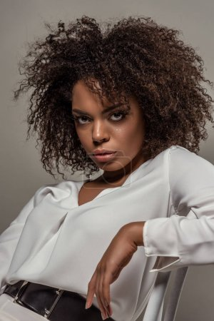 Young african american woman with seductive look in white shirt isolated on grey background