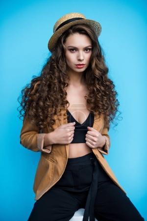 ernste junge Frau mit Kanuhut und Jacke, die isoliert auf blauem Grund in die Kamera blickt