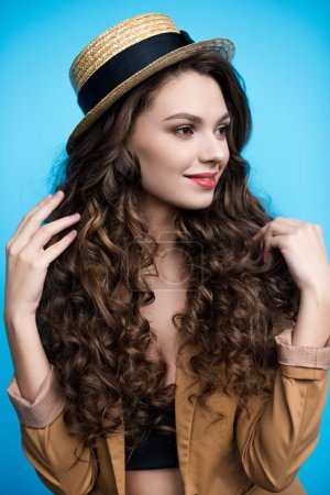 attractive young woman with long curly hair in canotier hat and jacket