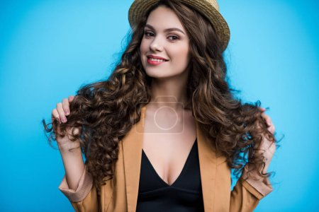 Photo for Happy young woman with long curly hair in canotier hat and jacket - Royalty Free Image