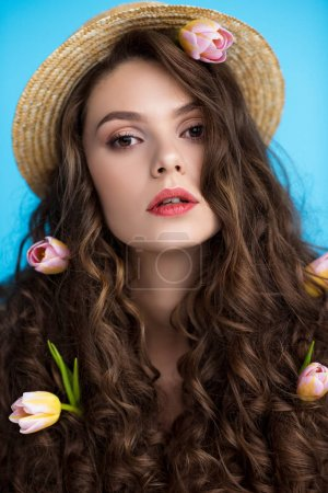 close-up portrait of young woman in canotier hat with flowers in her long curly hair looking at camera