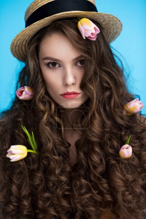 serious woman in canotier hat with flowers in her long curly hair looking at camera