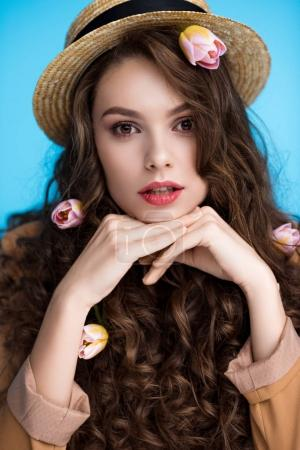 beautiful young woman in canotier hat with flowers in her long curly hair looking at camera