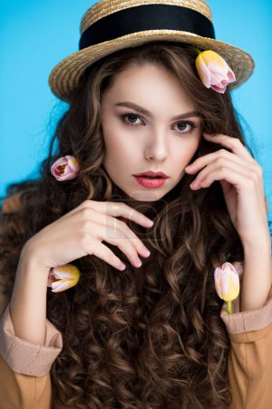 sensual young woman in canotier hat with flowers in her long curly hair