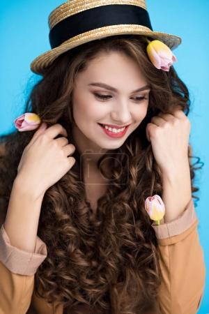 attractive young woman in canotier hat with flowers in her long curly hair