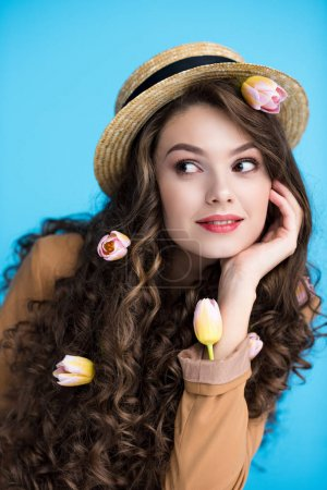 thoughtful young woman in canotier hat with tulips in her long curly hair
