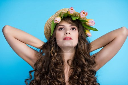 beautiful young woman in straw hat with pink tulips under it isolated on blue