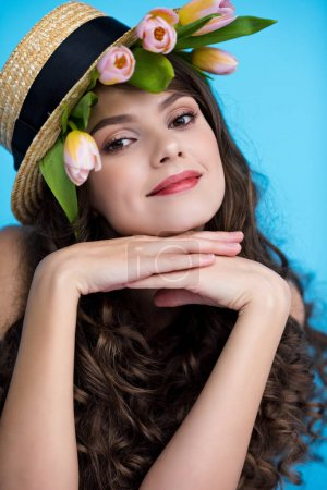 happy young woman in canotier hat with tulip flowers under it
