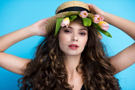 attractive young woman in canotier hat with pink tulips under it