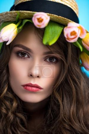 attractive young woman in canotier hat with beautiful tulips under it