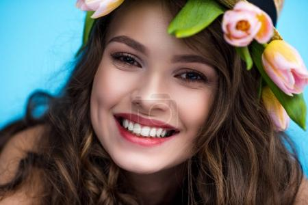 close-up portrait of happy young woman with wreath made of tulip flowers