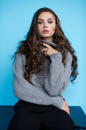 stylish long haired young woman with flowers on face in sweater sitting on table isolated on blue