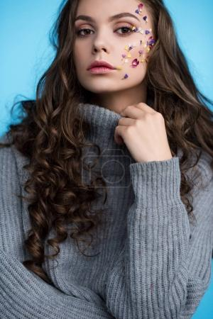 stylish long haired young woman with flowers on face in sweater