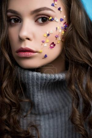 close-up portrait of stylish young woman with flowers on face in grey knitted turtleneck sweater
