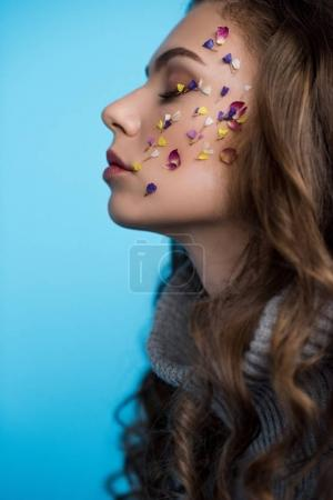 side view of young woman with flowers on face in sweater isolated on blue