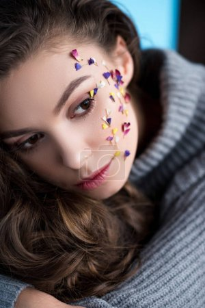 close-up portrait of woman with flowers on face in warm sweater