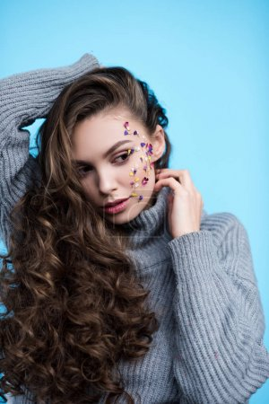 attractive young woman with flowers on face in warm knitted sweater isolated on blue