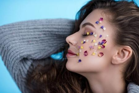happy young woman with flowers on face in warm sweater isolated on blue