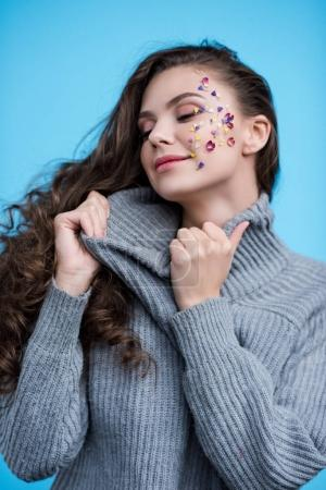 woman with flowers on face stretching neck of stylish sweater isolated on blue