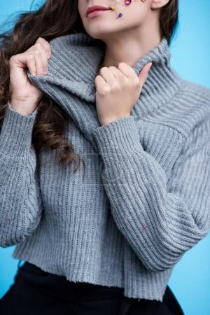 cropped shot of woman stretching neck of stylish sweater isolated on blue