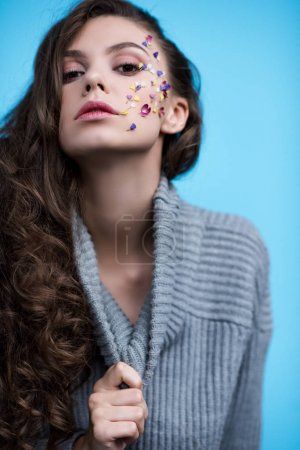 young woman in stylish turtleneck sweater with flowers on face isolated on blue