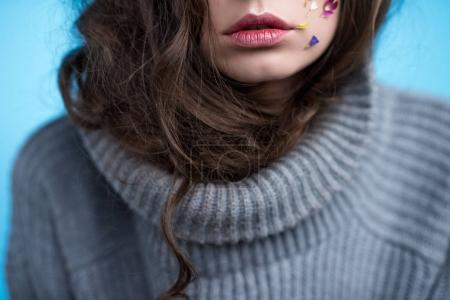 cropped shot of young woman in turtleneck sweater with flowers on face