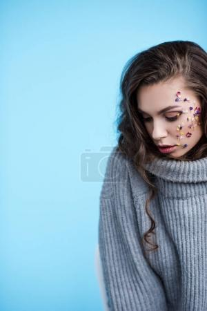beautiful woman in warm grey sweater and flowers on face isolated on blue