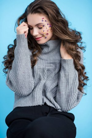 beautiful smiling brunette woman with flowers on face and closed eyes posing isolated on blue