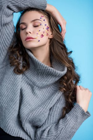 sensual young woman with closed eyes and flowers on face posing isolated on blue