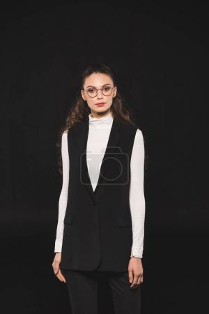 portrait of elegant stylish woman in eyeglasses looking at camera isolated on black