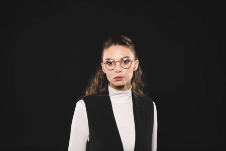 portrait of beautiful brunette woman in eyeglasses looking at camera isolated on black