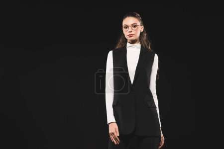 beautiful brunette woman in eyeglasses looking at camera isolated on black