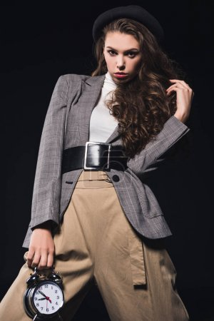 fashionable young woman holding clock and looking at camera isolated on black