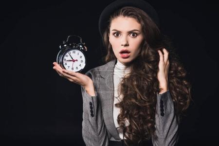 shocked young woman holding clock and looking at camera isolated on black