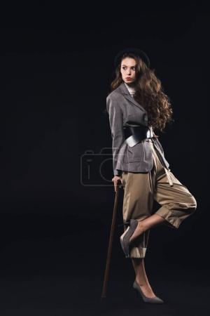 élégante jeune femme posant avec le bâton de marche et à la recherche de loin isolée sur noir