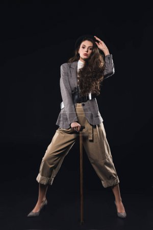 stylish young woman posing with walking stick and looking at camera isolated on black