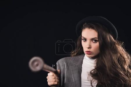 close-up view of stylish woman with walking stick looking at camera isolated on black