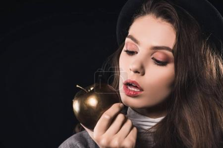 beautiful fashionable young woman eating golden apple isolated on black