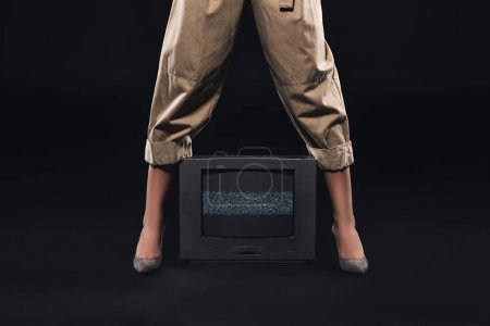 low section of stylish woman standing with tv with noises on the screen on black