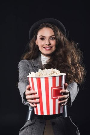 beautiful elegant young woman holding popcorn and smiling at camera isolated on black