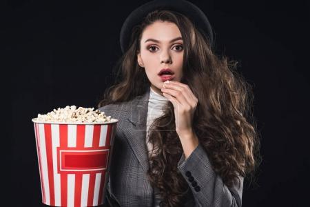 shocked fashionable young woman eating popcorn and looking at camera isolated on black