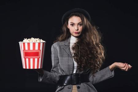beautiful stylish young woman holding popcorn and looking at camera isolated on black