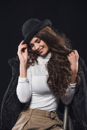 smiling young woman in stylish hat and winter jacket sitting on ladder isolated on black