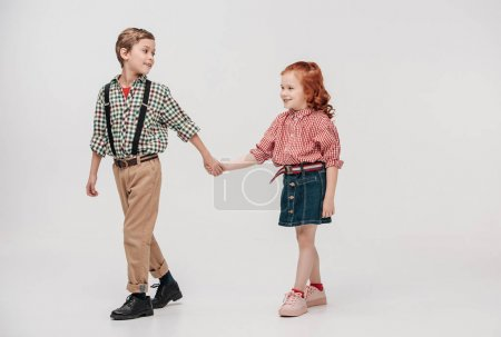 adorable little kids holding hands and walking together isolated on grey