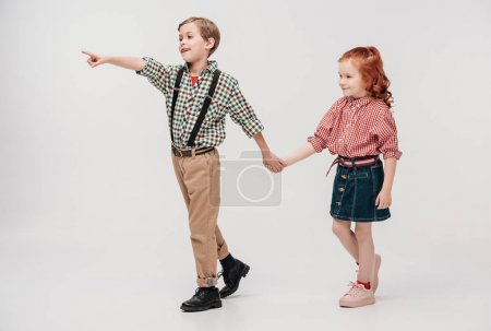 cute little kids holding hands and pointing away with finger isolated on grey