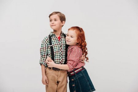 cute little children embracing and looking away isolated on grey