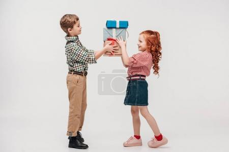side view of beautiful smiling children holding presents isolated on grey