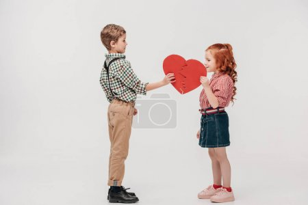 side view of cute little couple holding parts of broken heart isolated on grey