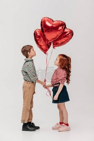 side view of beautiful little couple holding heart shaped balloons isolated on grey